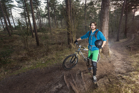 off road biking: Young man standing in the forest posing proudly with his ATB bike