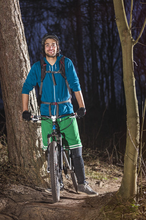 off road biking: Young man posing on his ATB in the forest in the late afternoon
