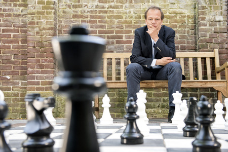 chess piece: Concentrated man, thinking strategically about his next move, sitting on a wooden bench in front of a brick wall during an outdoor chess game using life sized chess pieces and chess board