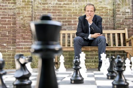 chess: Hombre concentrado, pensando estratégicamente sobre su próximo movimiento, sentado en un banco de madera delante de una pared de ladrillos durante un juego de ajedrez al aire libre mediante la vida de tamaño piezas de ajedrez y tablero de ajedrez