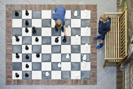 Two children playing a game of outdoor chess, seen from above