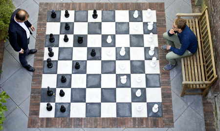 above: Two men playing a game of outdoor chess with large pieces, seen from above Stock Photo