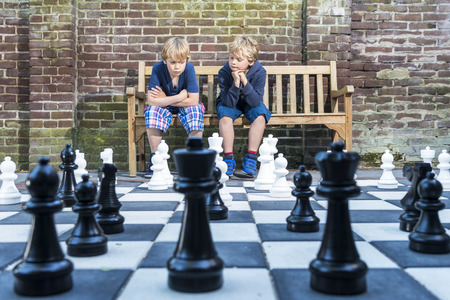 mind game: Two boys, sitting on a wooden bench, concentratedly thinking about their next move during an outdoors chess game with life sized pieces.
