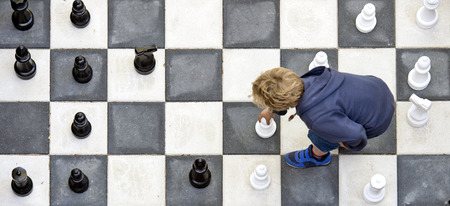 big game: Young boy moving a white pawn during a chess game on an outdoor chess board, seen from above Stock Photo