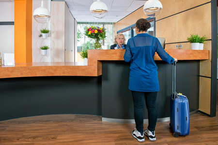Young woman with a carry on bag at a check in desk, where a female attendant offers information and assistance