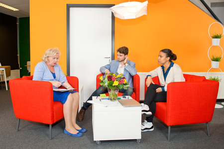 informal: Small project team meeting in a stylish, modern lobby of an office building, between two young associates and a senior reintegrated woman.