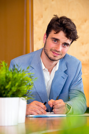 kindly: Young, eager apprentice, taking notes and learning on the job, wearing a blue jacket, looking kindly into the camera Stock Photo