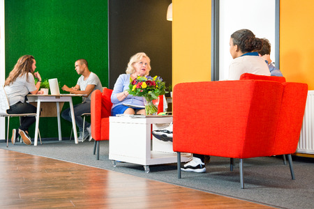 informal: Several people sitting in a business lounge during informal meetings and project team conferences Stock Photo
