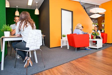 gente sentada: Vest�bulo y la zona de usos m�ltiples de espera, con varios grupos de personas que se sientan en las mesas durante las reuniones informales de una oficina de estilo moderno Foto de archivo