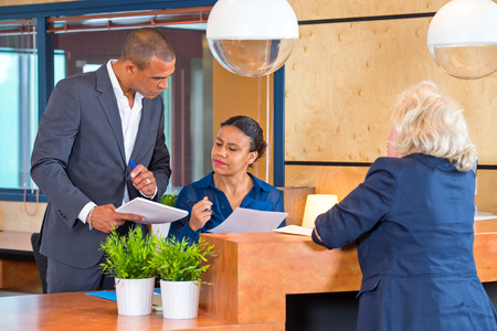 sorting out: Coworkers discussing small matters with a secretary at a reception desk of a large corporate company