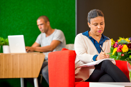 corporate culture: Young woman, taking notes and writing down ideasin a corporate lobby annex lounge on casual friday