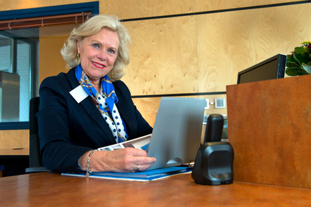 front desk: Smiling senior receptionist sitting at the front desk as an example of successful reintegration after retirement.