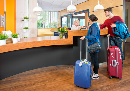 front desk: Young couple at the check in counter of a hotel,having just arrived with their luggage from the airport Stock Photo