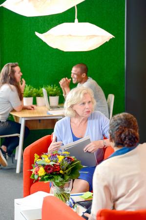 reuniones empresariales: Varios grupos de la conversación durante una reunión informal en una colorida sala de espera  vestíbulo de una oficina moderna Foto de archivo