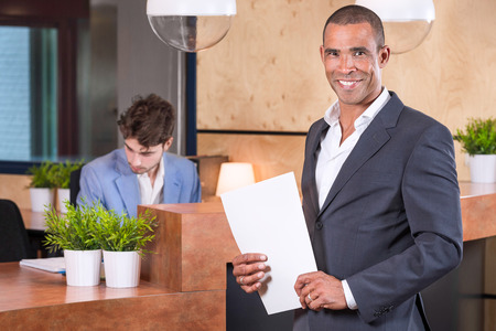carreer: Handsome businessman with documents in front of the reception
