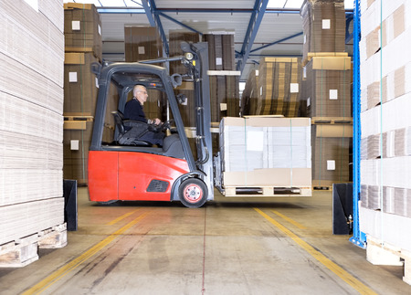 warehouses: Male worker carrying goods on forklift in distribution warehouse
