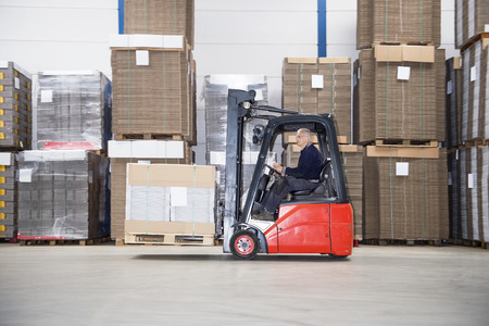 stockpile: Side view of male supervisor driving forklift by stockpile in warehouse Stock Photo