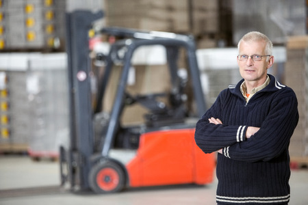 Portrait of confident supervisor with arms crossed standing at distribution warehouse Stock Photo