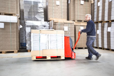 transporting: Side view of worker transporting goods on handtruck at distribution warehouse Stock Photo