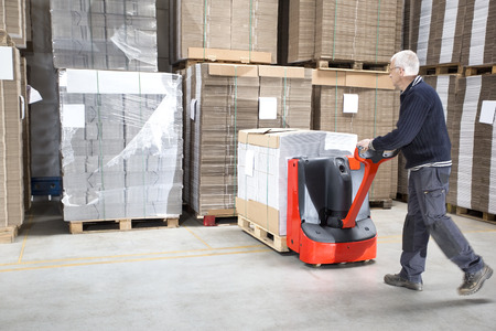 handtruck: Side view of male worker pushing stock on handtruck at distribution warehouse