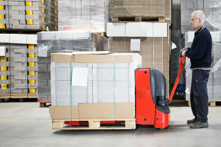 handtruck: Side view of worker standing by loaded handtruck in distribution warehouse