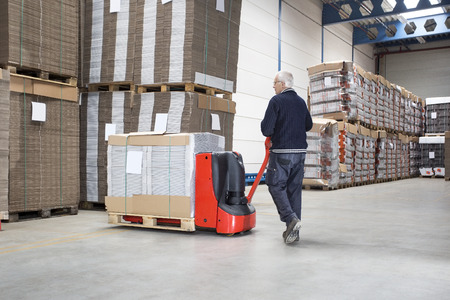 handtruck: Rear view of male worker pushing handtruck loaded with goods at distribution warehouse