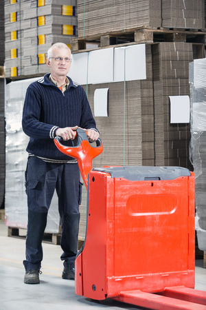 handtruck: Full length portrait of confident male worker standing with handtruck at warehouse