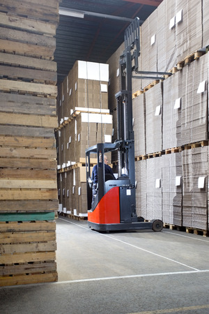stockpile: Rear view of supervisor examining stockpile while sitting in forklift at distribution warehouse