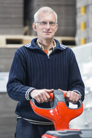 handtruck: Portrait of confident male worker holding handtruck while standing at warehouse