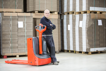 handtruck: Full length portrait of confident worker standing arms crossed while leaning on handtruck at warehouse