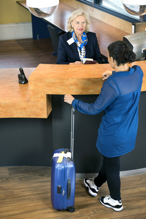standing reception: High angle view of woman with luggage standing at hotel reception desk