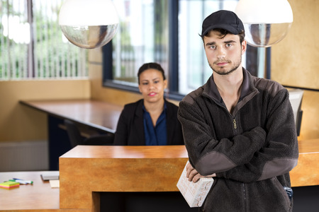 reception counter: Portrait of delivery man holding package while standing at reception counter in office Stock Photo