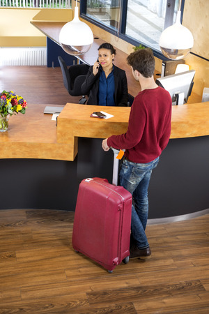 standing reception: High angle view of man with luggage standing at hotel reception desk