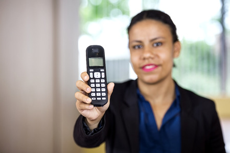 cordless: Portrait of smiling female receptionist holding cordless phone in office