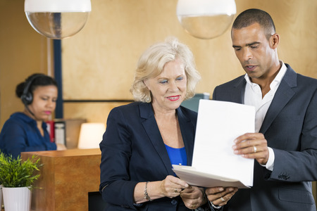 front desk: Businesspeople discussing over documents in front of reception desk at office Stock Photo