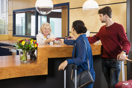 Couple giving passports to receptionist at counter in hotel