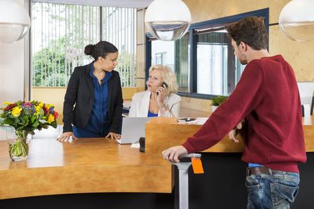 recepcionista: Hombre mirando al recepcionistas mujeres discutiendo en el mostrador en el hotel