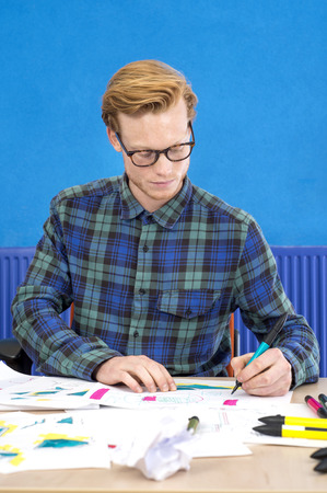 creative artist: Confident male artist making design on paper at desk in creative office
