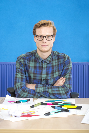 creative artist: Portrait of confident artist sitting with arms crossed at desk in creative office