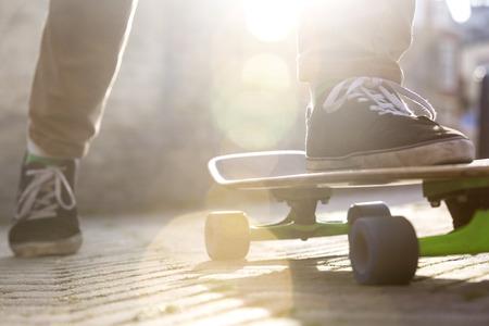 skateboarding: Low section of man skateboarding on footpath