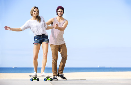 assisting: Full length of man assisting woman on skateboard at beach with clear blue sky in background Stock Photo