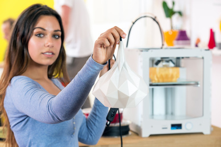 Female designer holding out a 3D printed lamp, that has just come off the printer
