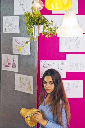 rapid prototyping: Young pretty designer, holding a 3D printed object, standing in front of a tackboard with design sketches