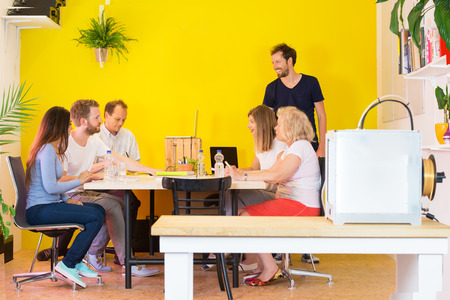 product development: Team of male and female designers discussing at desk in 3D printing studio