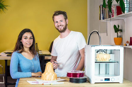 rapid prototyping: Two product designers, standing behind a table with a 3D Printing machine, discussing a new product and new technologies