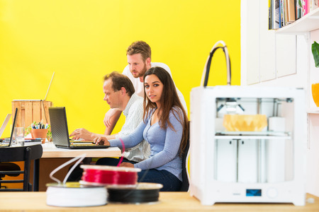 rapid prototyping: Portrait of female designer sitting with colleagues discussing in 3D printing studio