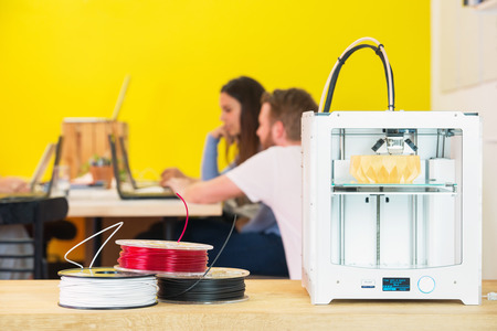 printing: 3D printing machine with product on counter with designers discussing in background at creative studio