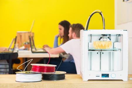 imprenta: M�quina de impresi�n 3D con producto en mostrador con dise�adores discutiendo en fondo en estudio creativo
