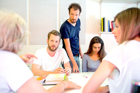 designer: Team of male and female 3D designers discussing at desk in printing studio