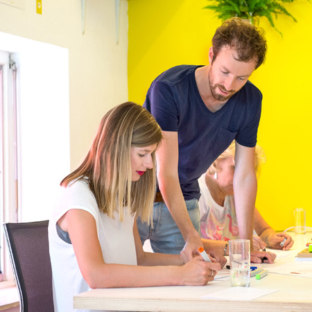 rapid prototyping: Male and female 3D developers discussing at desk in 3D printing studio Stock Photo